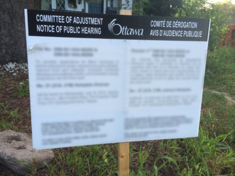 Blurred out Committe of Adjustment application sign on front lawn