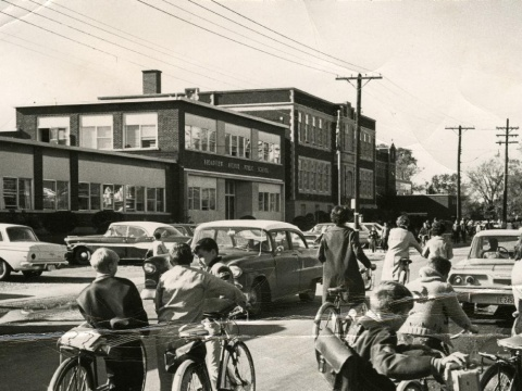 Black and white photo of kid on bicycles and vintage cars on the east side of Broadview Avenue Public School